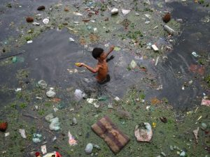 boy-throws-banana-after-collecting-it-from-the-polluted-waters-of-river-sabarmati-in-the-western-indian-city-of-ahmedabad_5141019
