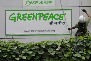 Activists of GreenPeace rappell down their office building where they are head quartered to unfurl banners 'democracy' and 'freespeech' in Bangalore on May 15, 2015. Greenpeace India, which is on the verge of closing down after the Indian government blocked its domestic accounts, is planning to appeal to the judiciary for relief. The NGO recently told its employees that the threat of an imminent shutdown is looming large as it has been left with cash reserves for salaries and office costs for just about a month. AFP PHOTO/ Manjunath KIRAN
