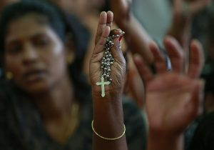869682-a-protester-holds-a-cross-during-a-protest-rally-by-hundreds-of-christians-against-recent-attacks-on